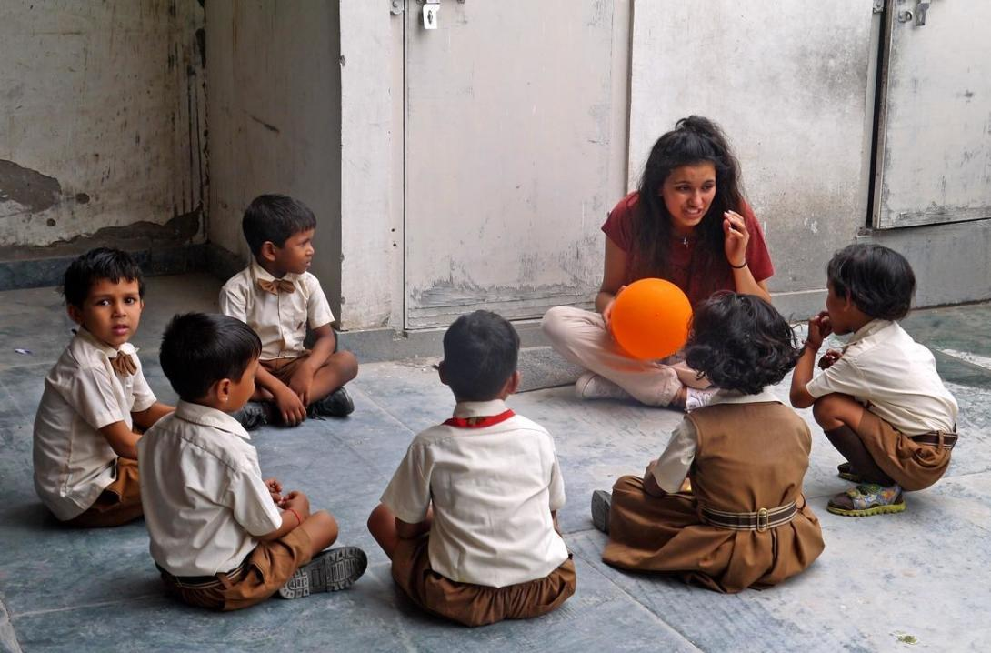 Childcare volunteer explains the rules of a ball game during her volunteer work experience with children in India.